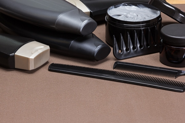 Hair products with few hair tools on a light brown surface