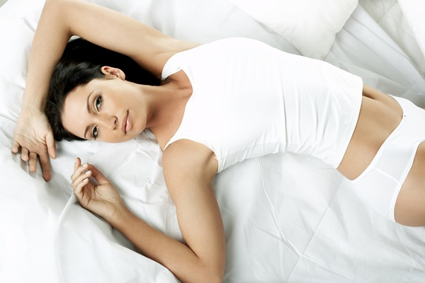 Woman with flawless body in white garment lying on her back